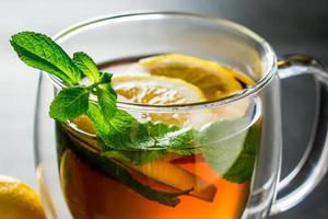 Tee mit Zitrone und Minze in einer Glasschale foto