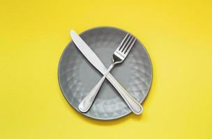 leere graue Platte und Besteck auf gelbem Hintergrund foto