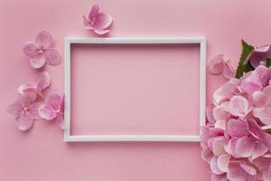 leerer weißer Rahmen auf rosa Hintergrund mit Blumen foto