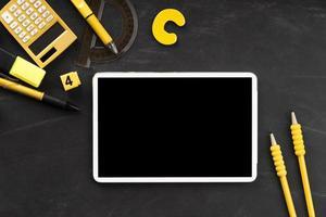 verspotten Sie digitales Tablett mit gelbem Schulmaterial auf schwarzem Hintergrund foto