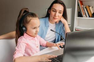 Mutter hilft Kind beim E-Learning foto