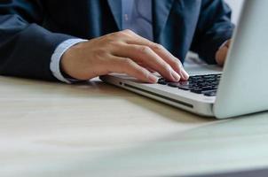 Geschäftsmann, der auf einer Tastatur tippt foto