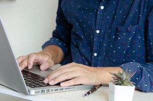 Mann, der auf einem Laptop tippt foto
