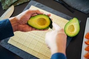 Person, die eine Avocado vorbereitet foto