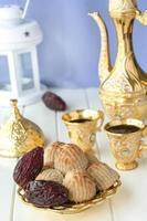 Ramadan-Konzept. Maamoul traditionelles arabisches gefülltes Gebäck oder Plätzchen mit Datteln oder Nüssen, serviert mit Kaffee goldenes Set. östliche Süßigkeiten. Nahansicht. weißer hölzerner Hintergrund. foto
