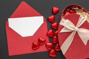Valentinstagskarte und Pralinen auf schwarzem Hintergrund foto