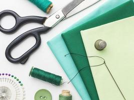 Stoff, Maßband, Nadeln und Faden zum Nähen foto