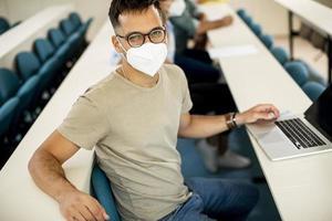 männlicher Student, der Gesichtsschutzmaske für Virenschutz im Hörsaal trägt foto