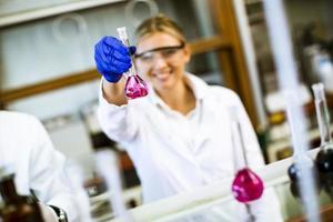 junge Wissenschaftlerin, die Flüssigkeit im biochemischen Labor untersucht foto