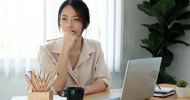 Frau denkt am Schreibtisch foto