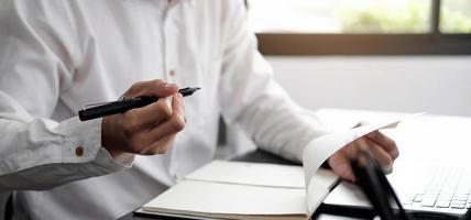Geschäftsmann bereitet sich darauf vor, in Notizbuch zu schreiben foto