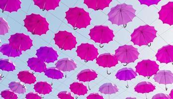 viele rosa Regenschirme, die in der Straße mit einem sonnigen Himmel hängen, 3d rendern foto