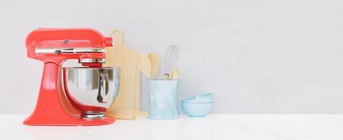 Küchenutensilien mit weißer Wand und Tisch und einem roten Küchenmixer vorne, 3D-Rendering foto