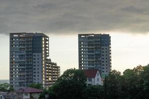 Stadtbild mit Baumhäusern, hohen Gebäuden und einem bewölkten Himmel in Sotschi, Russland foto