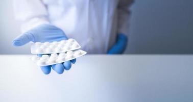 Apotheker, der Blisterpackung der weißen Pillen auf weißem Hintergrund und blauen Handschuhen anbietet foto