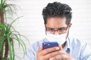 Mann, der eine Maske trägt und Telefon ansieht foto