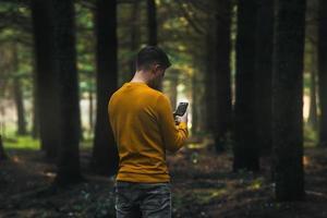 Person mit gelber Jacke und grauer Jeans, die sein Telefon im Wald betrachtet foto