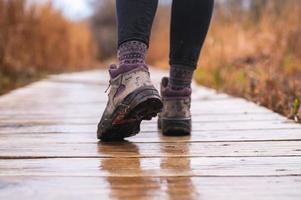 Mädchenfüße, die auf hölzerner Promenade mit Wanderschuhen am regnerischen Tag gehen foto
