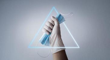 Hand hält Schutzmaske mit Handschuh und hellem Dreieck foto