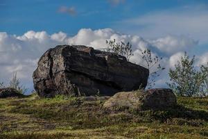 großer Felsen in einem grünen Feld in Russland foto