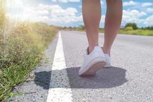 Frau, die auf kleiner Landstraße mit blauem Himmelhintergrund geht foto