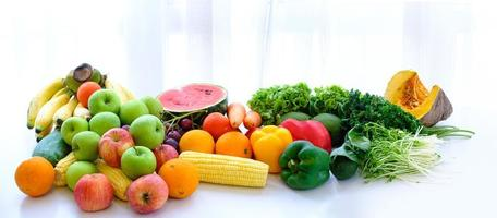 sortierte frisches reifes Obst und Gemüse auf dem Tisch mit weißem Vorhanghintergrund foto