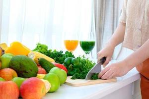 Hände mit einem Messer, das Gemüse über Holzschnitzbrett hackt foto
