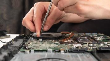 Nahaufnahme einer Person, die ein Teil auf einem Laptop-Motherboard ersetzt foto
