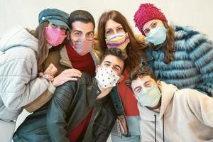 Gruppe junger Leute, die Gesichtsmasken tragen foto