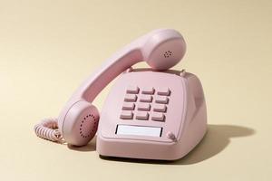 Vintage rosa Telefon auf gelbem Hintergrund foto