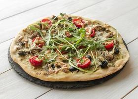 Arrangement einer leckeren Pizza mit Rucola und Tomaten foto