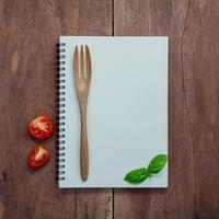 Notizbuch, süßes Basilikum, Kirschtomatenscheibe und Gabel auf dunklem schäbigem hölzernem Hintergrund foto