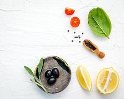 Lebensmittelhintergrund mit frischen Kräutern, Tomaten, Zitrone, schwarzem Pfeffer, Salbeiblättern, süßem Basilikum und Olivenöl über weißem Holzhintergrund foto