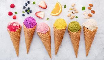 verschiedene Eiscremearomen in Zapfen auf weißem Steinhintergrund foto