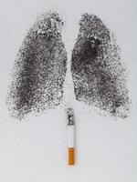 Form der Lunge mit Holzkohlepulver und Zigarette auf weißem Hintergrund foto