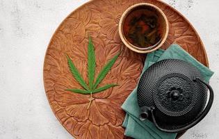 Weinlese-Teekanne mit Cannabis-Kräutertee und frischen Marihuana-Blättern, die auf Betonhintergrund aufgestellt werden foto