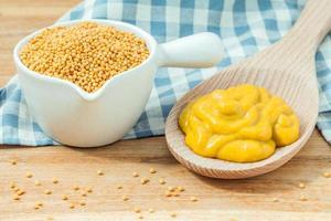 Zusammensetzung von Senf und Senfkörnern auf Holzhintergrund foto