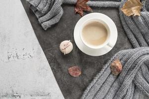 Kaffee mit Milch und warmem Pullover auf schäbiger Oberfläche foto