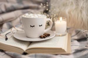 Tasse heißen Kakao mit Marshmallows auf Buch mit Kerze foto