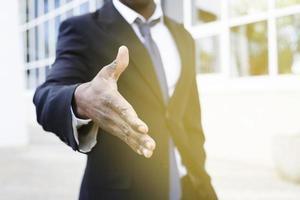 eleganter Geschäftsmann, der mit der Hand ausstreckt foto