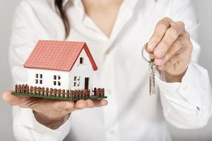 Frau hält ein Spielzeugmodellhaus und Schlüssel foto