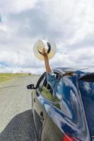 weibliche Hand, die Hut aus beweglichem Autofenster heraushält foto