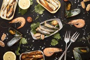flaches Sortiment an Meeresfrüchten mit Besteck foto