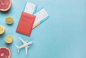 Flatlay-Flugkonzept mit Obst, Pass und Modellflugzeug auf blauem Hintergrund foto