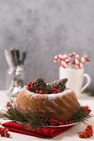 Vorderansicht des Weihnachtskuchens mit Tannenzapfen und roten Beeren foto