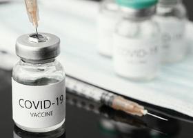 Covid-19-Impfstoff in Flaschen mit Spritzen foto