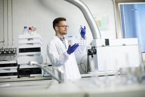 junge Forscher arbeiten mit chemischen Proben im Labor mit hplc-System und Chromatographie-Ausrüstung foto