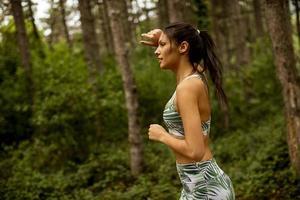 junge Fitnessfrau, die am Waldweg läuft foto