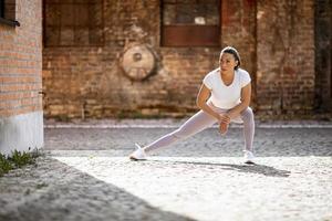 junge Frau, die sich während des Trainings in der städtischen Umgebung ausdehnt foto