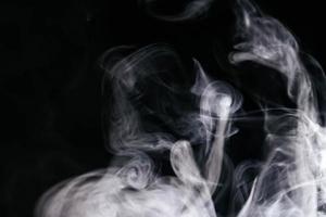 grauer Rauch winkt schwarzen Hintergrund foto
